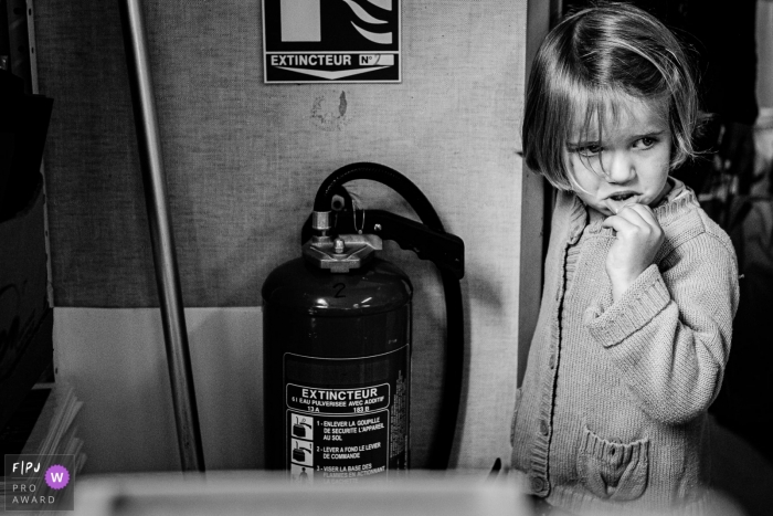 Moment driven Occitanie family photojournalism image in BW of a shy girl at school