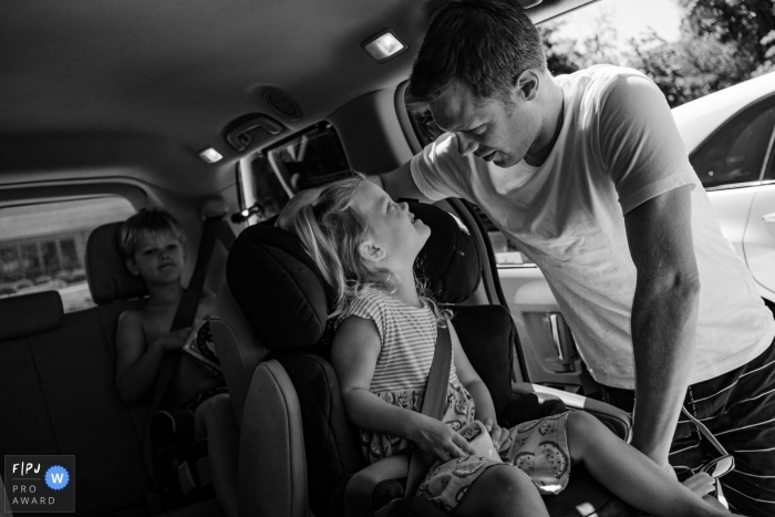 Moment-driven SF, CA family photography with dad helping with getting buckled in