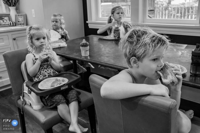Moment driven San Francisco family photojournalism image in BW around the kitchen table at Breakfast time