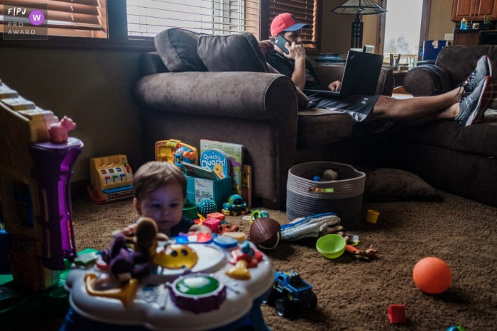 Moment driven San Francisco family photojournalism image of dad and child busy in the living room