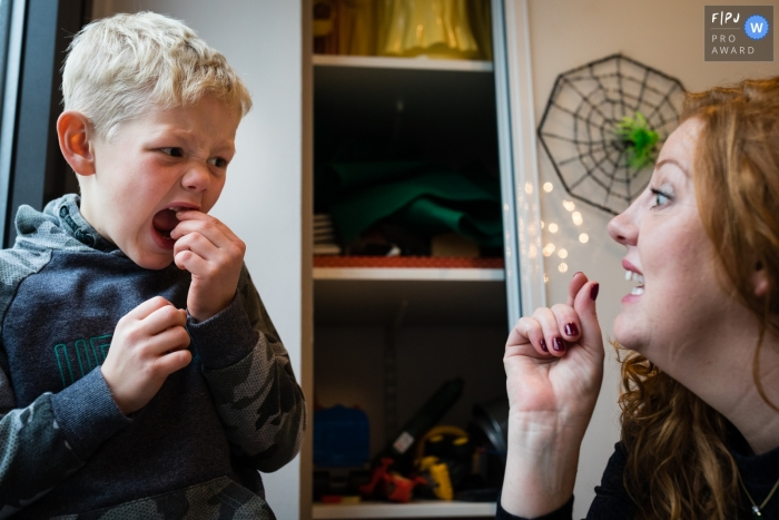 Moment driven Cambridgeshire family photojournalism image showing Mum helps son who has a lose tooth and looks anxious, by suggesting he twist it
