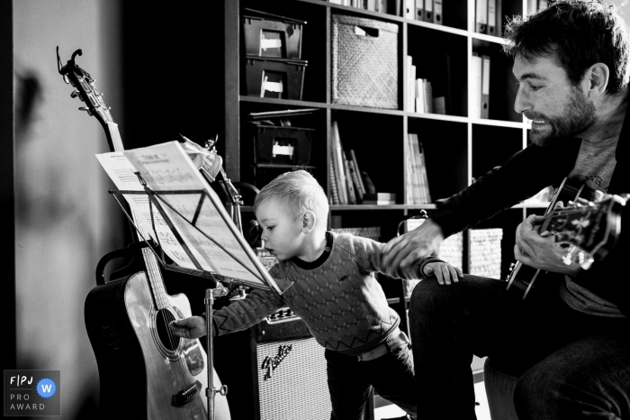 Moment driven Belgium family photojournalism image in BW of dad playing music on guitars with young son