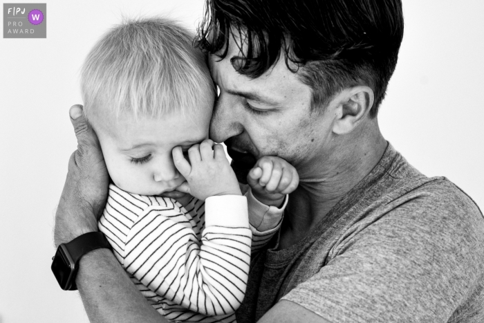 Moment-driven Belgium family photography with father holding toddler in BW