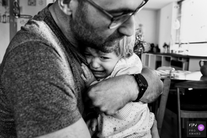 Moment-driven East Flanders family photography with dad and child hugging during a day in the life photo session