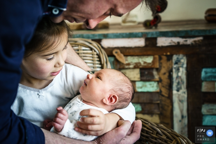 Moment-driven Centre-Val de Loire family photography showing dad and his daughter are looking to the baby