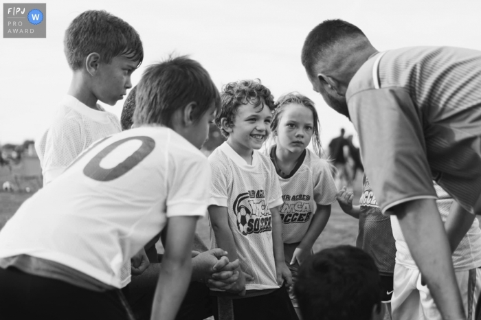 Moment driven Joplin family photojournalism image during Soccer season and first game huddle