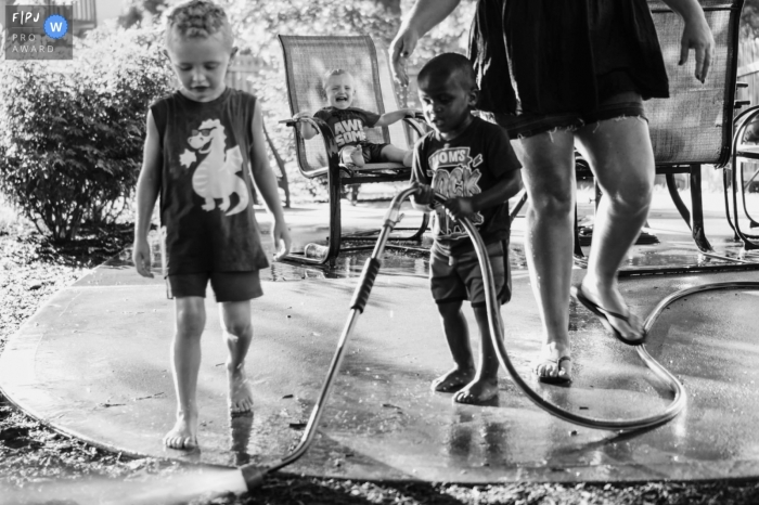 Moment-driven Joplin family photography in BW showing Brothers playing the sprinkles and fighting over the hose and One little guy got put into a time out