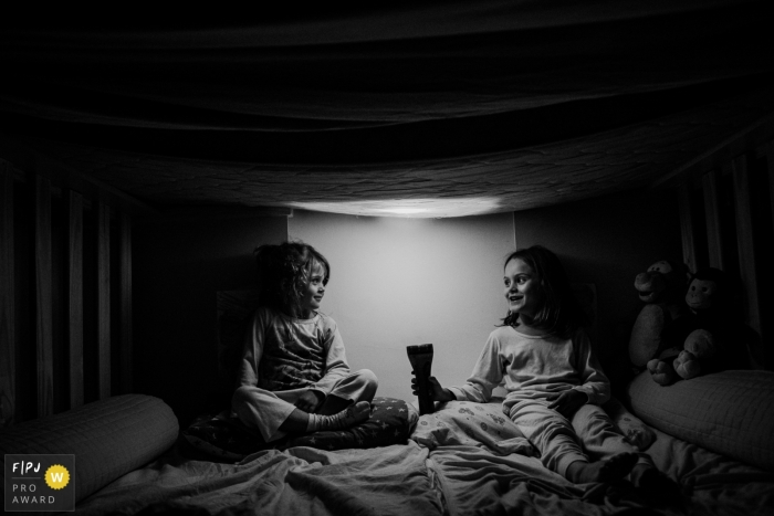 Moment-driven Sao Paulo children photography showing two sisters in a tent / bed with flashlight at night