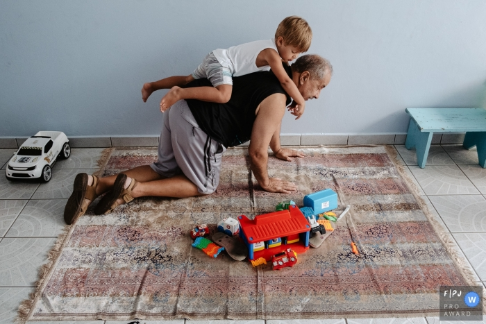 Moment-driven Florianopolis family photography of a Grandfather playing with his grandson who climbs on his back