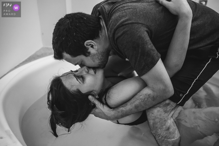 Belo Horizonte father holds his wife carefully, showing her love during her painful labor in a birth tub