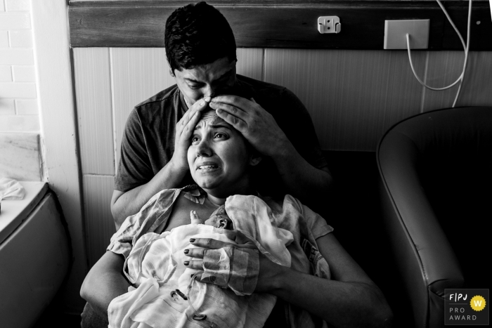 Maternidade Ilha birth image of a very emotional mother as she holds her new baby and is being kissed on his head by her husband