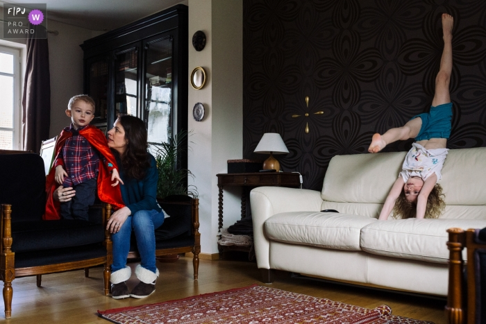 Paris family photography of mom with kids, one doing gymnastics in the living room