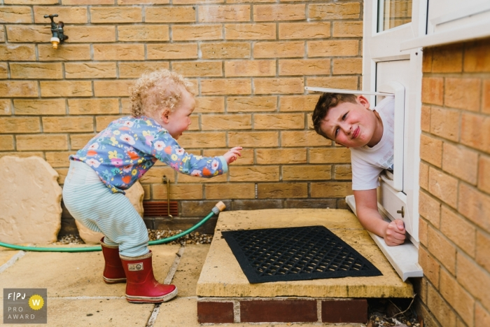 Norfolk family photo of a young boy stuck in the dog door flap