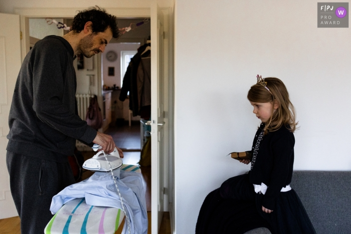 Hamburg father ironing a shirt as his daughter watches