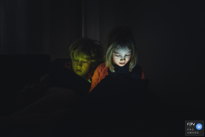 Amsterdam family photo of a boy and girl looking at an iPad with their faces lit up in the dark