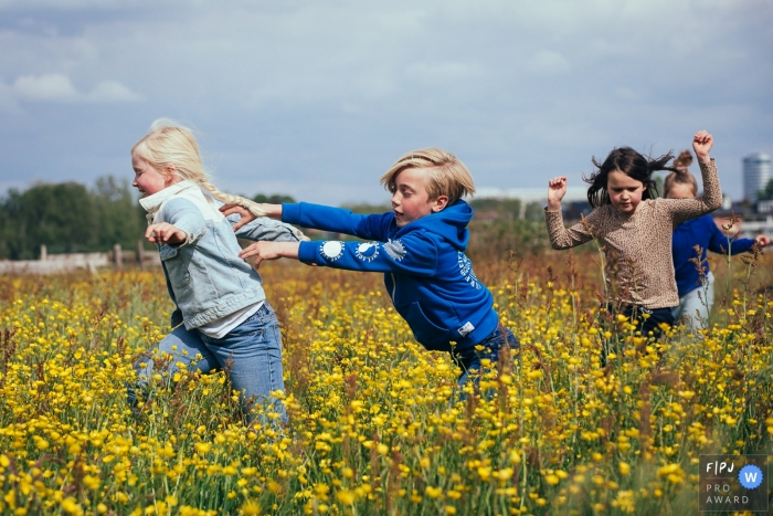 Amsterdam children playing catch in a spring flower field during a family photo session