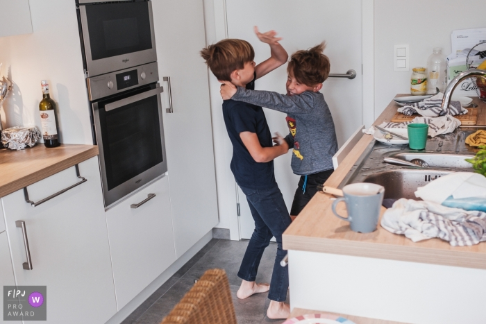 Two brothers fighting in the kitchen captured by Antwerpen photographer during a family session