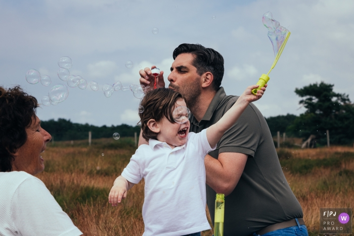 Amsterdam family shoot with a grandma, father and son playing with bubbles