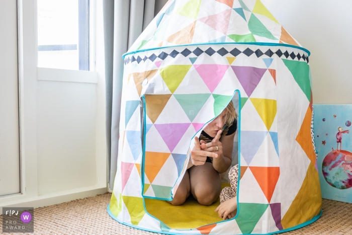 Gelderland family playtime photography of a mother with daughter in tent telling her to be quiet