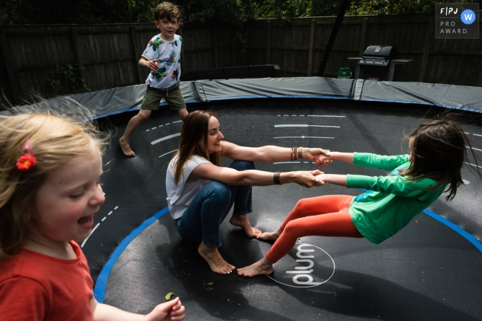 Cambridgeshire family and children photography of a mum playing with her children on trampoline