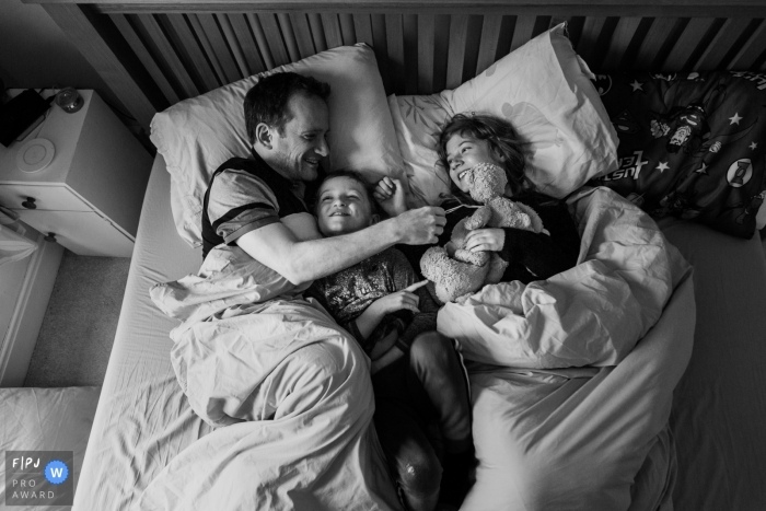 Bath family image of a father and his children having some quiet time together in bed