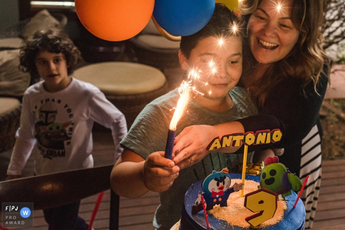 Campo Grande family birthday party photography of a boy celebrating with cake and a candle