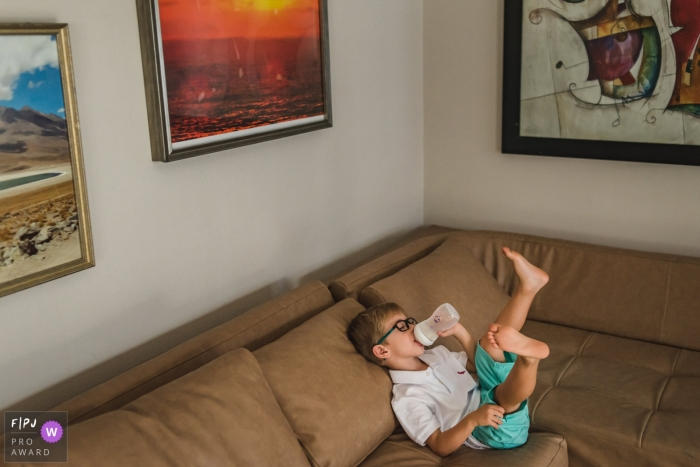 Campo Grande family photography coverage of boy enjoying the baby bottle on the sofa
