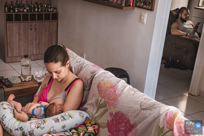 Campo Grande day in the life photo of mother nursing her child, with dad in the other room resting