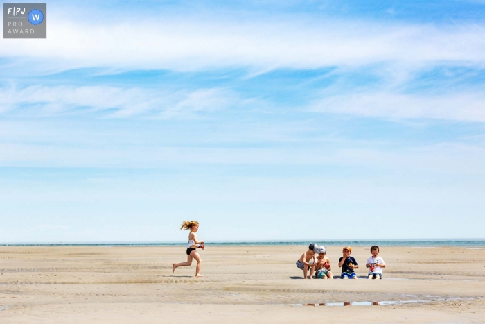 New Hampshire family photography of a ittle girl as she runs on the beach towards four friends who are snacking on the sand