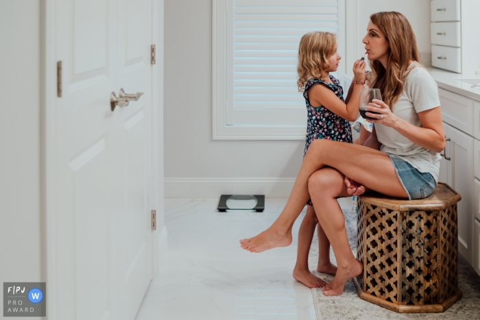 New Hampshire at-home family coverage of a little girl as she puts makeup on mom in bathroom