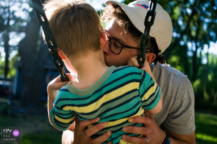 Atlanta backyard family shoot of a father kissing his son on the swing