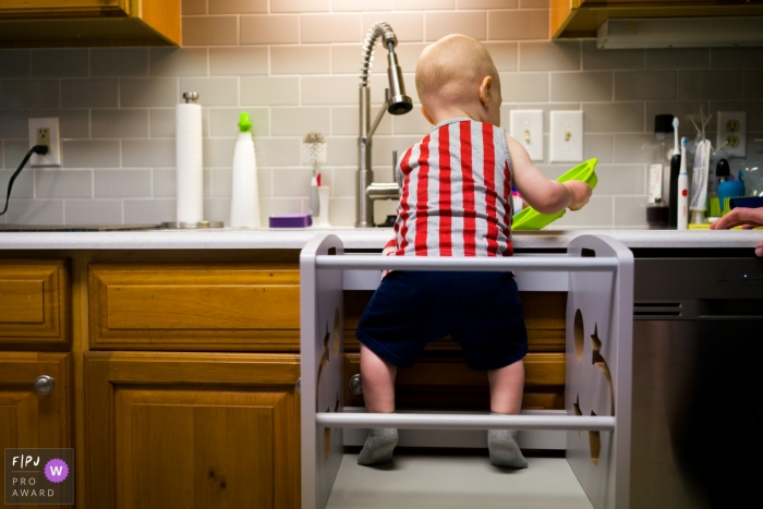Atlanta at-home photo of a baby boy washing dishes in the sink